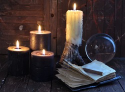 Creepy still life with burning candles, crystal ball and open diary on witch table. Esoteric, wicca and occult background with magic objects, fortune telling and divination ritual, Mystic background