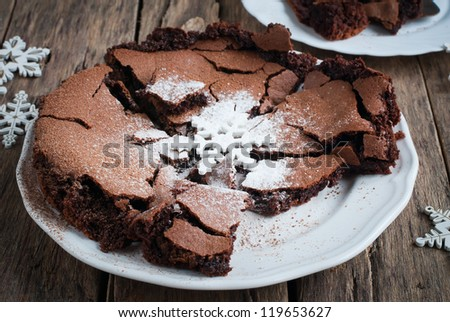 Crisp Chocolate Pie on a White Plate Decorated by a Snowflake and Powdered Sugar