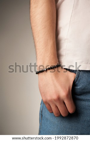 Cropped close-up shot of male wrist with beaded bracelet made of black ornamental stone and decorated with metal beads and charm with letter B. Man in beige t-shirt put his hand in the pocket.        Stok fotoğraf ©