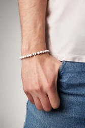 Cropped close-up shot of male wrist with beaded bracelet made of white marble stone and decorated with silver beads and charm with letter G. Man in beige t-shirt put his hand in the pocket.