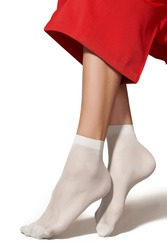 Cropped shot of female legs in white nylon semi-opaque socks with reinforced toes and rims. The lady in red wide trousers is posing on tiptoe on the white background.