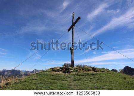 3269 Cross at the peak of Mount Setzberg against blue sky #1253585830
