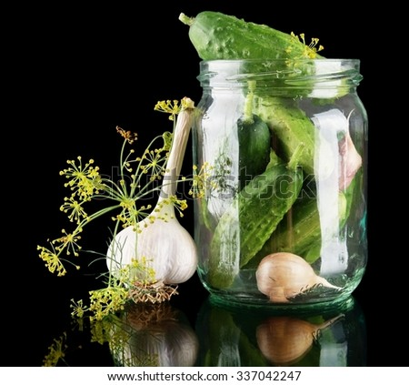 Cucumbers in jar preparate for pickling with flower bud,leaves,jar,garlic,dill flowers and tendrils isolated on black background