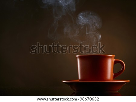 Cup of coffee over dark background