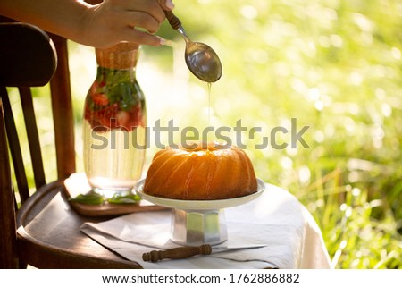 Cupcake with syrup.Cupcake with maple syrup.Agave syrup is pouring on a cupcake.Pie in the summer garden.A large muffin is poured with syrup. Beautiful pie in the summer garden on a chair. Dessert Photo stock ©