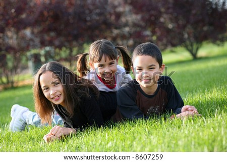 3 cute children of diverse nationalities outdoors