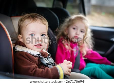 cute small children in car seats in the car