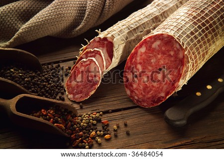 2 Cutted salami on wood table with spices - stock photo