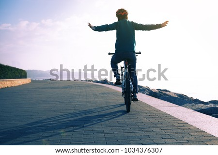 cycling enthusiast riding bike in the sunrise coast path