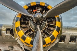 9 cylinder combustion engine with yellow, black square pattern. Nine chamber, air cooled radial motor with propeller closeup on heavy military bomber airplane or aircraft used in the second world war