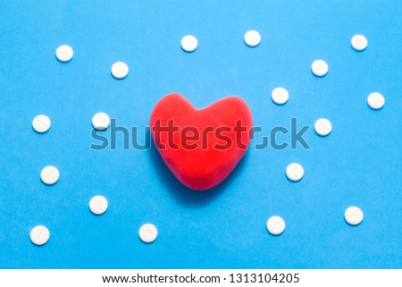 3D anatomical model of heart is on blue background surrounded by white pills as ornament polka dots. Medical concept by pharmacological tableted treating of heart and vessel disease, pharmacotherapy