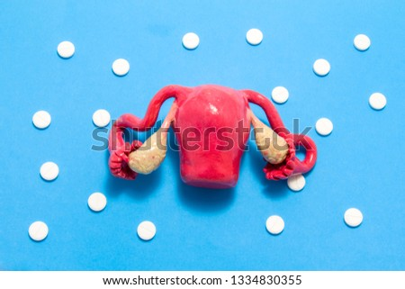 3D anatomical model of uterus with ovaries is on blue background surrounded by white pills as ornament polka dots. Medical concept by pharmacological tableted treating of uterus disease, chemotherapy