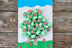 3D applique of colored paper, volume, spring tree with flowers, on a wooden background, handmade.
