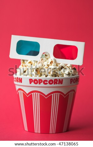 3D glasses on top of a bucket of popcorn - 3D cinema concept, shallow dof
