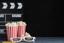 3D glasses, popcorn and clapboard on dark background, space for text