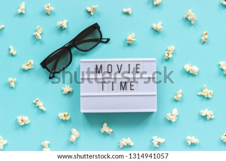 3D glasses, popcorn and lightbox text Movie time on blue paper background. Top view Template Concept cinema movie and entertainment.
