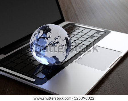 3D image of modern laptop and crystal globe on wooden desk