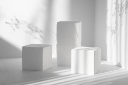3d podium, for presentations of packaging, cosmetics. Three white square scenes, of different heights, against background of clean walls with hard shadows from flowers. The concept of the beauty.