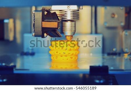 3d printer printing objects yellow form closeup. Modern technical 3D printing. #546055189