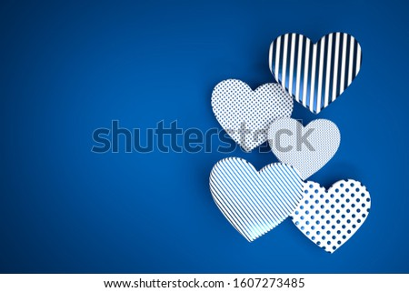 3D render: Differently textured hearts in classic blue on classic blue background. Wedding or valentines day card.