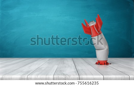 3d rendering of a red and silver realistic model of a retro rocket stands crashed into a wooden desk on a blue background. Failed launch. Technological progress. Technical mistake.