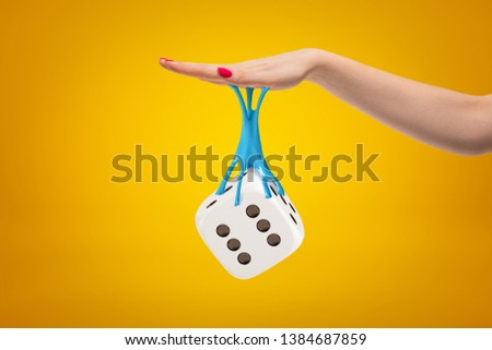 3d rendering of casino dice stuck with sticky slime to female hand on yellow background. Digital art. Objects and materials. People and objects.