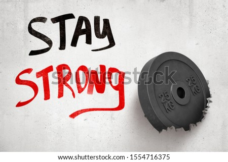 3d rendering of 25 kg weight plate breaking white wall with 'Stay strong' sign on white background. Games and sports. Outdoor activities. Sporting goods.