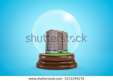 3d rendering of miniature brown multi-storey building inside snowglobe on light blue background. Construction business. Urban development. Modern city.