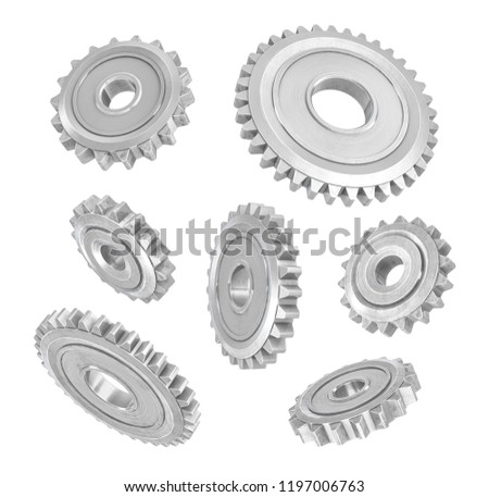 3d rendering of several metal spur gears hanging in different angles on a white background. Mechanical parts. Equipment internal parts. Changing gears.