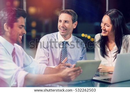 3D Smiling businessman discussing with colleagues over digital tablet in office