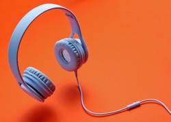 3D surround photo modern blue headphones with cable on orange background.
