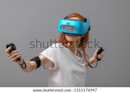 3d technology, virtual reality, entertainment, education concept. Young red-haired woman wearing white t-shirt using vr headset with head-mounted display, playing video game