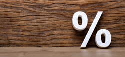 3D White Percentage Sign Against Wooden Wall