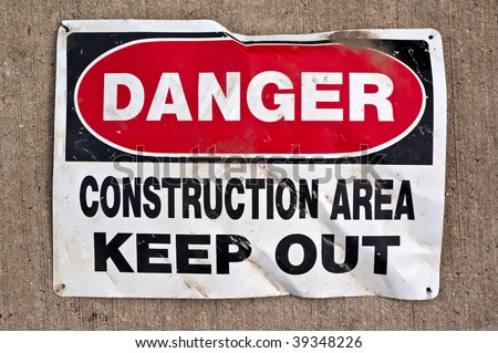 """Danger. Construction area. Keep Out"". Old crumpled sign laying on the concrete."