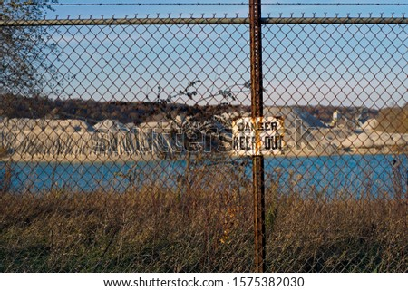 Danger keep out sign on the fence that keeps onlookers safe at a Limestone quarry in Delphi Indiana that supplies water to the Wabash and Erie canal
