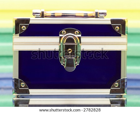 Dark blue steel small suitcase with the lock on a multi-coloured background.