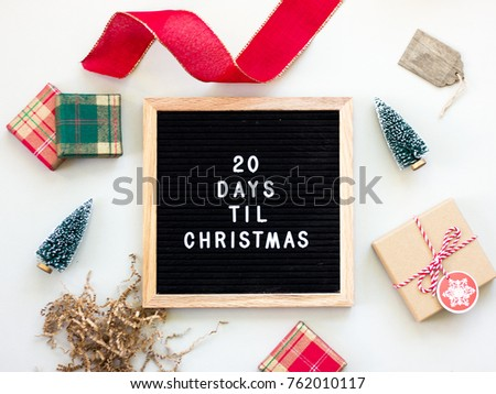 20 Days Til Christmas. Christmas countdown on a black letter board surrounded by Christmas objects. #762010117