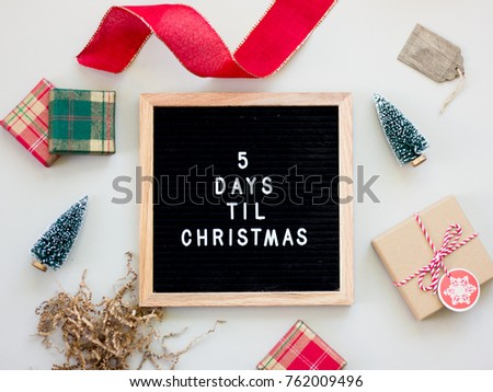 5 Days Til Christmas. Christmas countdown on a black letter board with wooden frame surrounded by holiday objects. #762009496