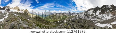 360 degree panorama taken in the mountains on top of the Furkapass in the Swiss Alps on a sunny day with a beautiful cloudscape