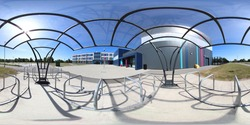 360 degree panoramic sphere photo of the Whitcliffe Mount Primary School showing a metal bike rack storage cage on a sunny summers day