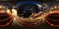 360 Degree spherical panorama sphere photo of the inside of an empty typical British theatre showing rows of empty  red chairs and a large open stage area below.