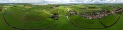 360 degrees aerial panorama of the agrarian green pasture fields with its irrigation infrastructure of ditches and trenches surrounding the small traditional village of Ransdorp near Amsterdam
