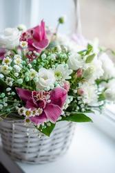 Delicate spring flower arrangement in a wicker basket. Flower arrangement for woman