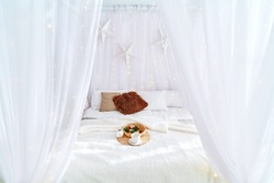 Delicate white interior design in boho style, with a white bed and a light canopy. Pillows, delicate and airy hanging stars. Breakfast in bed with coffee and delicious cookies, pine cones