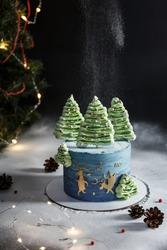 Delicious and beautiful Christmas cake decorated with bizet Christmas trees, sprinkled with powdered sugar in the form of snow on a black background. New Year's cheesecake