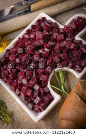 Delicious Fresh pieces of beet cube close-up with fresh onion and olive oil on a bag cloth on a rustic gray table. Beets are the root part of a beet plant.