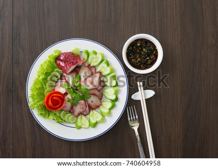 Delicious Roast red pork in white dish (Asian food) with black sauce on dark background  / Selective focus / Selective focus and space for messages