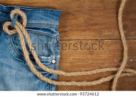 Denim Jeans with rope on a wood background