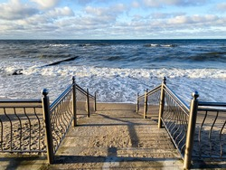 Descent to the sea. Stormy waves of the Baltic Sea at sunset. Pier.