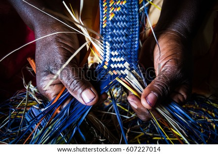 Detail of African woman's hands weaving blue and yellow raffia mat